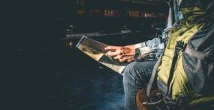 Viajero que se sienta y que mira en el mapa para el tren que espera la estación de tren Imágenes de archivo libres de regalías