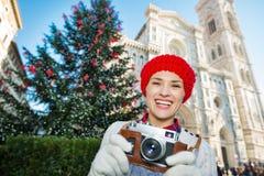 Viajero que sostiene la cámara de la foto cerca del árbol de navidad en Florencia Foto de archivo