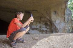Viajero que toma la foto del paisaje rocoso con el teléfono de la cámara de la cueva de la montaña Fotografía de archivo libre de regalías