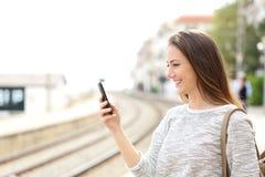 Viajero que usa un smartphone en una estación de tren Imagen de archivo libre de regalías