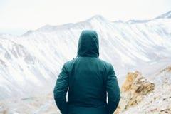 Viajero resuelto con las manos en escena permanente y de observación del bolsillo de la nieve de la montaña imágenes de archivo libres de regalías