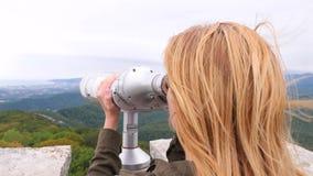 Viajero rubio de la mujer que mira a través de un telescopio encima de una montaña 4k, a cámara lenta metrajes