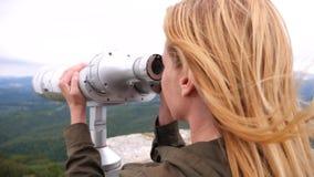 Viajero rubio de la mujer que mira a través de un telescopio encima de una montaña 4k, a cámara lenta almacen de video