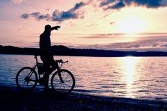 Viajero solo con la mochila Hombre en la playa del mar en el banco de madera, tarde soleada fría del otoño imagenes de archivo