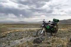Viajero solo del enduro de la motocicleta con las maletas que se colocan en meseta rocosa en tiempo nublado Fotos de archivo libres de regalías