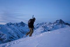 Viajero valiente con la mochila y una snowboard detrás el suyo montaña trasera del invierno de las subidas Fotografía de archivo libre de regalías