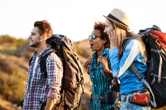 Viajeros alegres jovenes con las mochilas sorprendidos, sonriendo, caminando en barranco Imagen de archivo libre de regalías