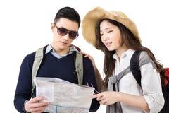 Viajeros asiáticos jovenes de los pares que miran el mapa Imagen de archivo libre de regalías