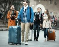 Viajeros con equipaje que hacen turismo y que sonríen en otoño fotografía de archivo