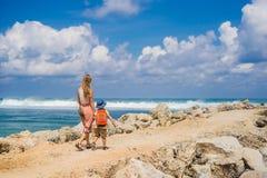 Viajeros de la mamá y del hijo en sorprender la playa de Melasti con agua de la turquesa, isla Indonesia de Bali El viajar con co imagen de archivo