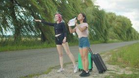 Viajeros de las mujeres que hacen autostop con la muestra de la cartulina almacen de metraje de vídeo
