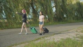 Viajeros diversos de las mujeres que hacen autostop en el camino rural almacen de video
