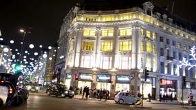 Viajeros en las compras de la Navidad con las decoraciones en la calle en Londres, Reino Unido