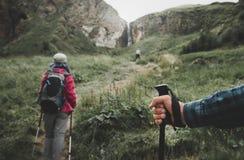 Viajeros en las montañas, emigrando a poste en la mano de un primer de la persona del viajero Concepto de las vacaciones de la fo fotos de archivo