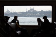 Viajeros en un transbordador en Estambul con el hagia Sophia y la mezquita de Sultan Ahmet foto de archivo libre de regalías