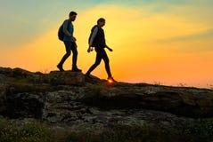 Viajeros felices jovenes que caminan con las mochilas en Rocky Trail en la puesta del sol del verano Concepto del viaje y de la a fotos de archivo