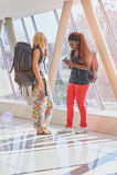 2 viajeros femeninos en vestíbulo del aeropuerto que comprueban el teléfono Imágenes de archivo libres de regalías
