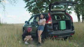 Viajeros femeninos que comprueban hacia fuera el neumático plano en el coche almacen de video