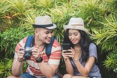 Viajeros jovenes que toman un resto en el lado del camino durante su foto de archivo libre de regalías