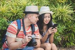 Viajeros jovenes que toman un resto en el lado del camino durante su fotos de archivo libres de regalías