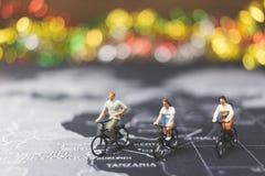 Viajeros miniatura de la gente que montan la bicicleta en mapa del mundo Fotos de archivo