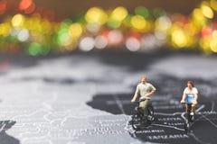 Viajeros miniatura de la gente que montan la bicicleta en mapa del mundo Fotografía de archivo libre de regalías