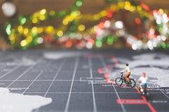 Viajeros miniatura de la gente que montan la bicicleta en mapa del mundo Imagen de archivo libre de regalías