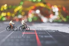 Viajeros miniatura de la gente que montan la bicicleta en mapa del mundo Imagenes de archivo