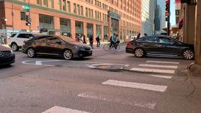 Viajeros a pie y en los coches que viajan durante hora punta en el lazo céntrico de Chicago almacen de metraje de vídeo