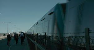 Viajeros que cruzan el puente para conseguir el hogar, una tranvía del metro de Estocolmo que pasa cerca almacen de video