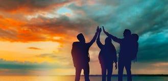 Viajeros que hacen arriba cinco sobre puesta del sol ilustración del vector