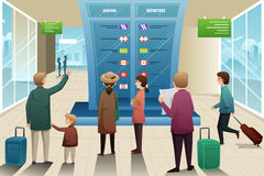 Viajeros que miran al tablero de la salida Foto de archivo libre de regalías