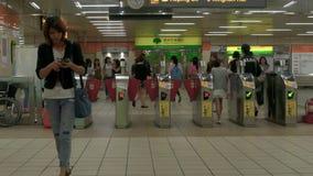 Viajeros que pasan a través de las puertas del boleto en el sistema del subterráneo del MRT de Nanshijiao en la nueva ciudad de T almacen de video