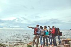 Viajeros que se colocan en la costa que busca la nave fotografía de archivo