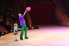 Viajes del circo de Moscú en el hielo Payaso con el globo y poco gir Imagen de archivo