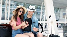 Viajes Pares usando el teléfono y el sentarse cerca del terminal de aeropuerto almacen de metraje de vídeo