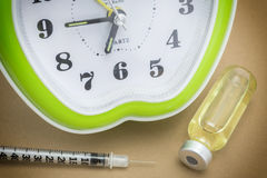 Vial and green clock. Daily medication treatment Stock Photo