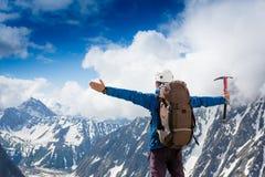 Viandante alla cima di una roccia con le sue mani sollevate Immagine Stock