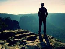 Viandante alta sul picco della roccia dell'arenaria che guarda sopra la valle nebbiosa e nebbiosa di mattina per esporre al sole  Fotografie Stock Libere da Diritti