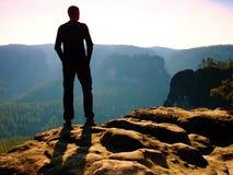 Viandante alta sul picco della roccia dell'arenaria che guarda sopra la valle nebbiosa e nebbiosa di mattina per esporre al sole  Fotografia Stock Libera da Diritti
