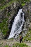 Viandante che cammina davanti alla cascata Fotografie Stock Libere da Diritti