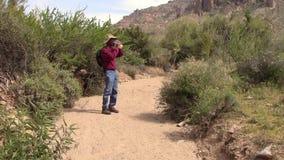 Viandante che cammina in lavaggio del deserto ed acqua potabile. archivi video
