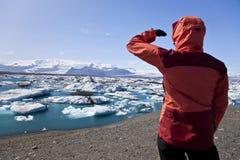 Viandante che esamina Jokulsarlon, laguna, Islanda Fotografia Stock