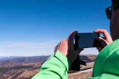 Viandante che fotografa il paesaggio con il telefono cellulare Fotografia Stock