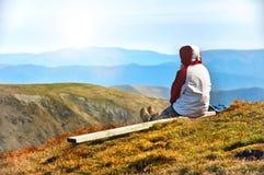 Viandante che gode della vista della valle dalla cima di una montagna Fotografie Stock