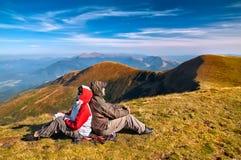 Viandante che gode della vista della valle dalla cima di una montagna Fotografie Stock Libere da Diritti