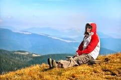 Viandante che gode della vista della valle dalla cima di una montagna Immagine Stock