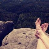 Viandante che guarda paesaggio collinoso sopra le proprie gambe pelose fotografie stock