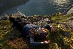 Viandante che ha un resto dopo la scalata della montagna, Lofoten, Norvegia Immagine Stock