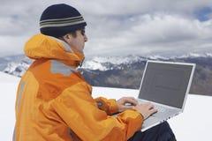 Viandante che per mezzo del computer portatile sul paesaggio della montagna di Snowy Immagini Stock Libere da Diritti